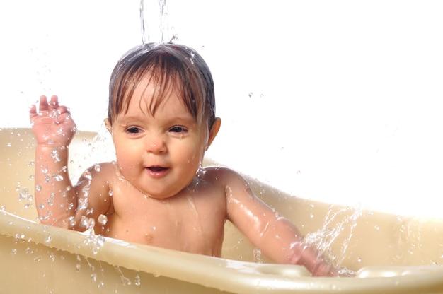 Nettes kleines nasses babyporträt, das das bad nimmt