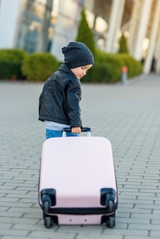 Nettes kleines reisendes mädchen zieht rosa koffer zum flughafen.