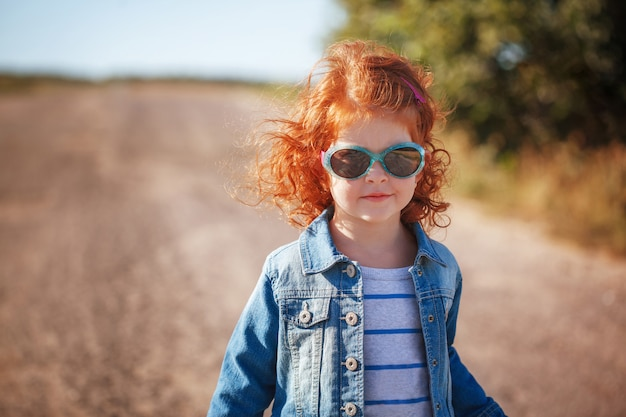 Nettes kleines rotes gelocktes mädchen des porträts in der sonnenbrille am sonnigen tag