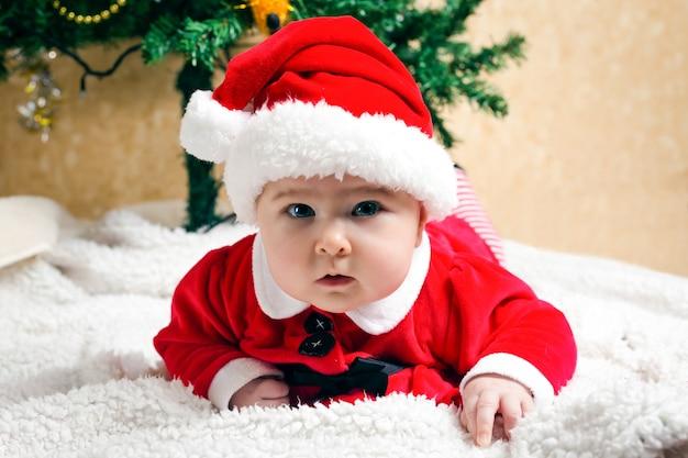 Nettes kleines weihnachtskind, das weihnachtsmannanzug trägt und und den betrachter, weihnachtsbaum am raum betrachtet
