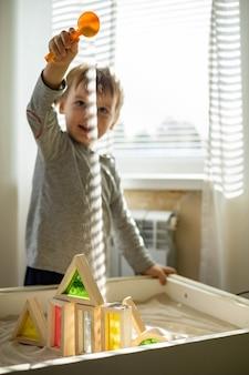 Nettes kleinkind, das kinetische sandbox zur selbstentwicklung spielt, verwendet die maria-montessori-methode