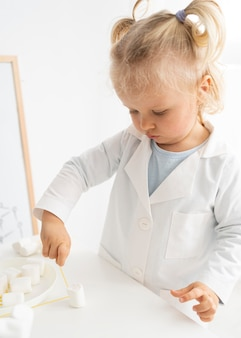 Nettes kleinkind, das mit marshmallows und nudeln etwas über wissenschaft lernt