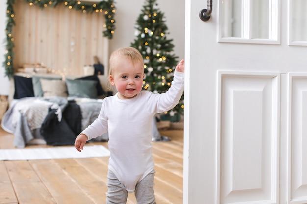 Nettes kleinkind im schlafzimmer mit weihnachtsbaum