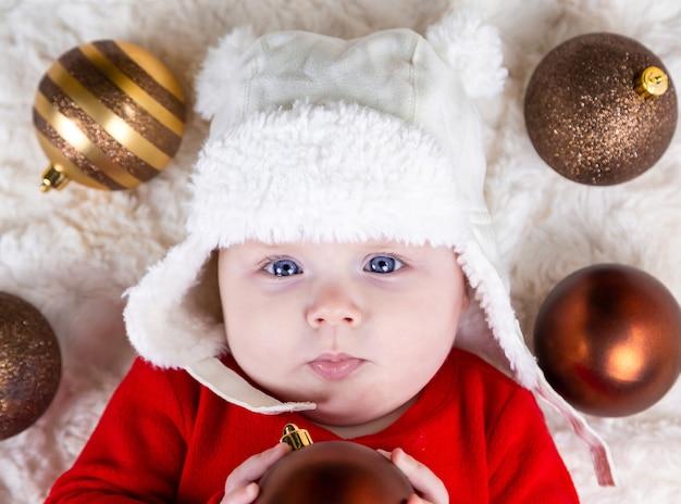 Nettes kleinkind mit weihnachtsball, auf dem boden liegend. süßes kleines mädchen in einem roten kleid und weißem hut drückt gefühle aus. weihnachtskonzept mit kleinem kind