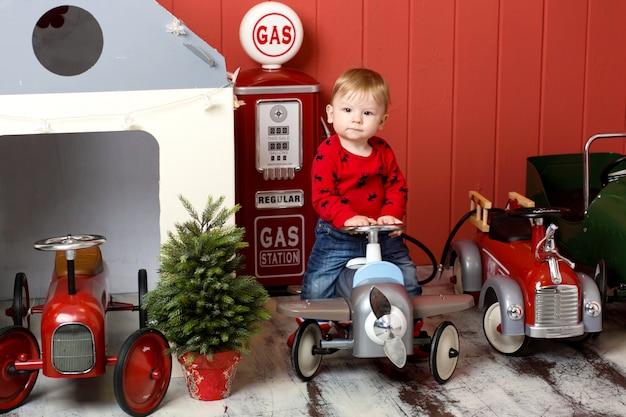 Nettes kleinkind spielt mit spielzeugautos. fährt ein spielzeug-schreibmaschinenflugzeug. glückliche kindheit