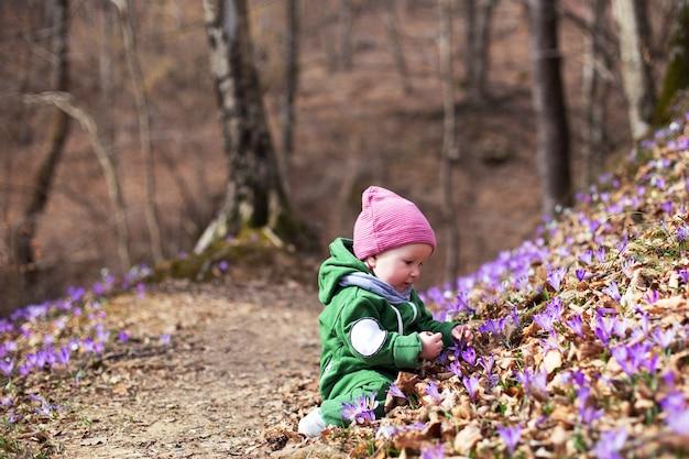 Nettes kleinkindbaby, das grünen overall und rosa hut im frühlingswald voller wilder iris trägt. frühlingsblüte im wald. harmonie, hoffnung und frieden