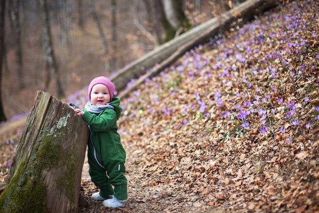 Nettes kleinkindbaby, das grünen overall und rosa hut im frühlingswald voller wilder iris trägt.