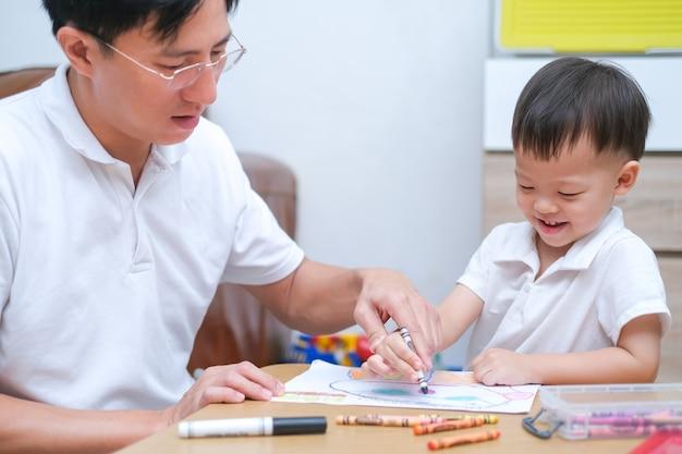 Nettes kleinkindjungenkind, das mit buntstiften kind malt, das mit vater zu hause färbt