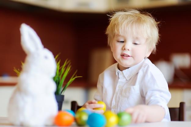 Nettes kleinkindkind, das für osterei am ostertag jagt