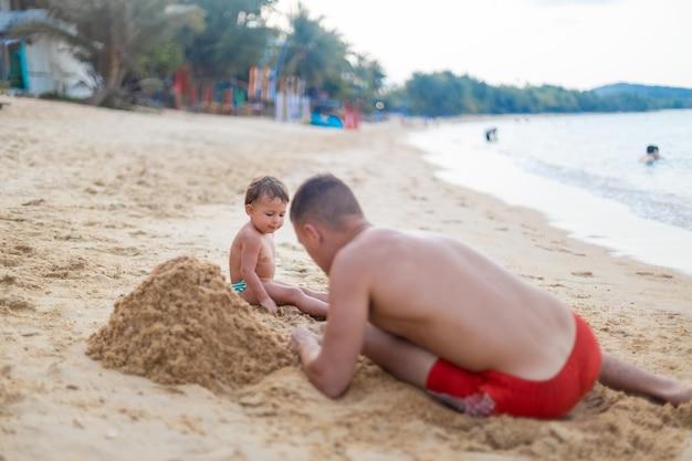 Nettes kleinkindkind, das mit vater am meer im sand spielt