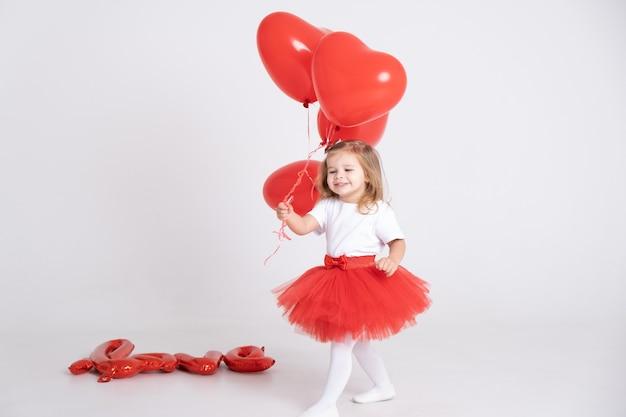 Nettes kleinkindmädchen, das herzballons mit inschriftenliebe von luftballons auf einem weißen hintergrund hält.
