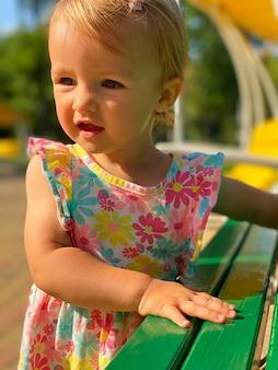 Nettes kleinkindmädchen im kleid mit blumendruck, das weg auf die parksommerzeit schaut
