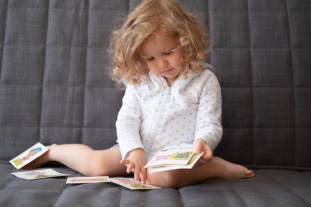 Nettes kleinkindmädchen spielen mit frühen entwicklungskarten, die auf der couch sitzen. kinder farbige flash-karten. spielzeug für kleine kinder. kind mit pädagogischem spielzeug.