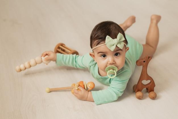 Nettes kleinkindmädchen von 8 monaten liegt auf dem holzboden des hauses und spielt mit holzentwicklungsspielzeug. foto in hoher qualität