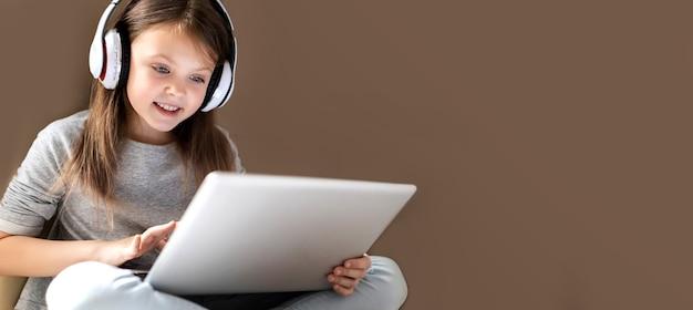 Nettes kluges kleines mädchen in drahtlosen kopfhörern mit laptop zu hause