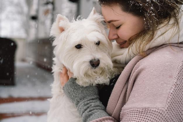 Nettes lachendes mädchen, das entzückenden weißen hund mit lustigen niedlichen gefühlen umarmt. west highland white terrier. adoptionskonzept.