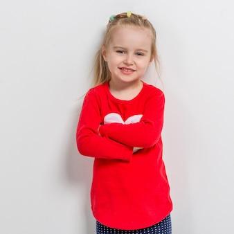 Nettes lachendes mädchen in der roten strickjacke