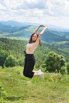 Nettes lachendes mädchen springt gegen den hintergrund von bergen und von wäldern.