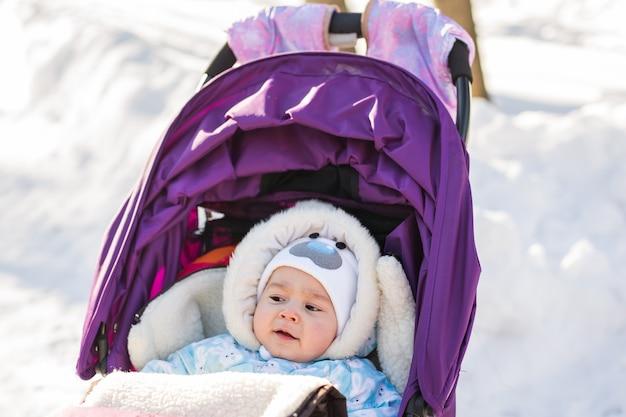 Nettes lächelndes baby, das an einem kalten wintertag in einem kinderwagen sitzt.
