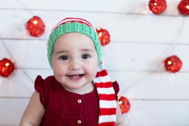 Nettes lächelndes baby, das weihnachtsmütze auf verziert für neujahrshintergrund trägt. rote, grüne und weiße farben