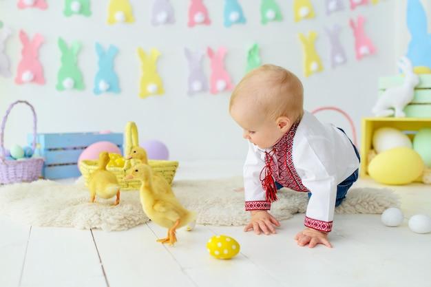 Nettes lächelndes baby in traditioneller stickerei in farbigen osterdekorationen