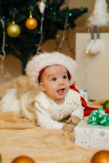 Nettes lächelndes baby liegt unter einem festlichen weihnachtsbaum und spielt mit geschenken. weihnachts- und neujahrsfeier.