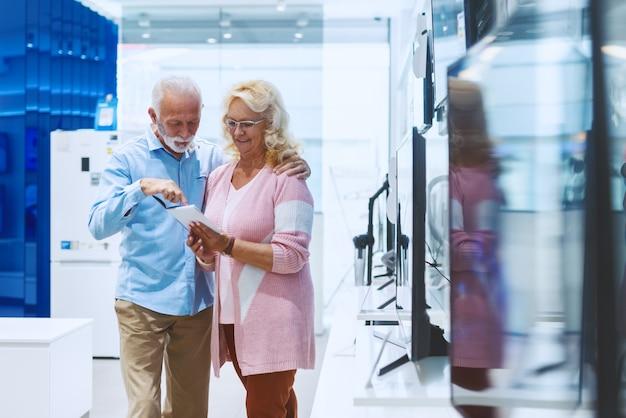 Nettes lächelndes kaukasisches älteres paar, das im technologieladen steht und preise für fernsehen betrachtet, das sie kaufen wollen.
