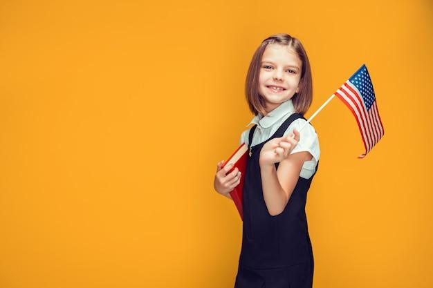 Nettes lächelndes kaukasisches schulmädchen, das amerikanische flagge und buch auf gelber hintergrundflagge usa hält