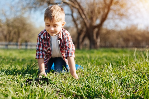 Nettes lächelndes kind, das im gras draußen in einem familienlandhaushof spielt