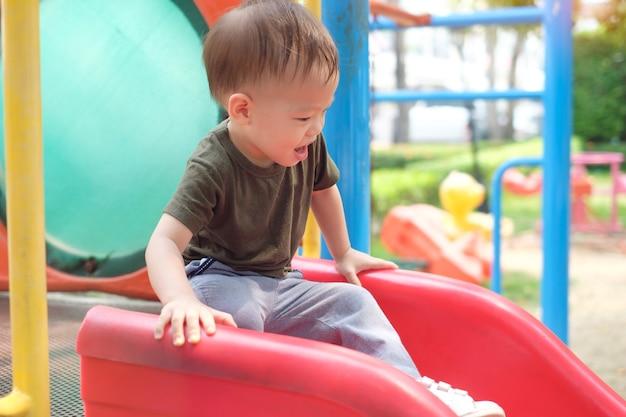 Nettes lächelndes kleines asiatisches 1-jähriges kleinkind, das auf einer rutsche auf dem spielplatz spielt