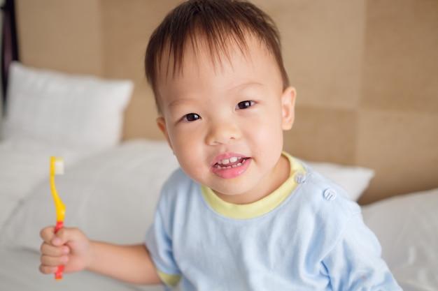 Nettes lächelndes kleines asiatisches 30 monate / 2 jahre altes kleinkindjungenkind, das pyjama im bett sitzt, das zahnbürste hält und lernt, zähne am morgen zu hause zu putzen, zahnpflege für kinderkonzept