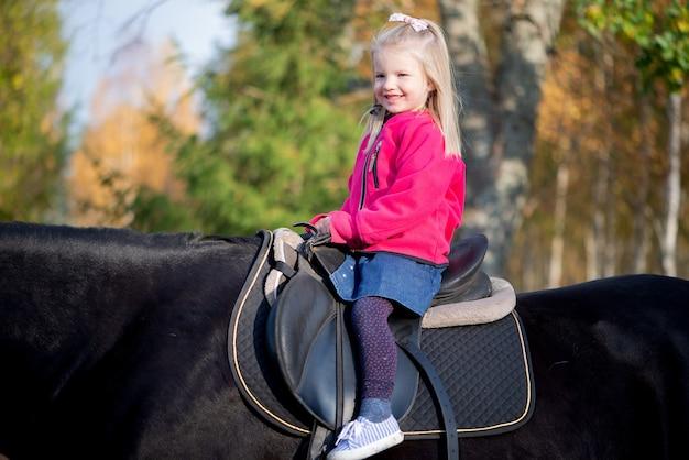 Nettes lächelndes kleines mädchen, das auf schwarzem pferd reitet