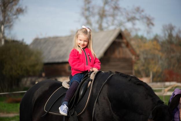 Nettes lächelndes kleines mädchen, das auf schwarzem pferderücken reitet