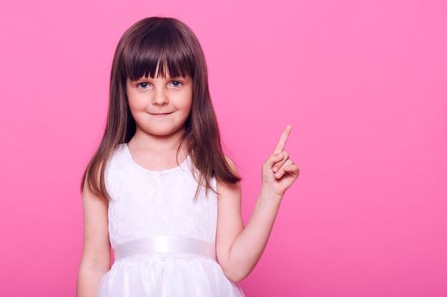 Nettes lächelndes kleines mädchen, das weißen zeigefinger weg zeigt, während es mit ruhigem und zufriedenem gesichtsausdruck nach vorne schaut, kopiert raum für beförderung, lokalisiert über rosa wand
