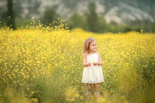 Nettes lächelndes kleines mädchen mit blumenkranz auf der wiese an der farm. porträt des entzückenden kleinen kindes im freien. hochsommer. tag der erde