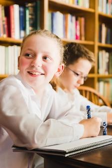 Nettes lächelndes mädchen am schreibtisch in der bibliothek