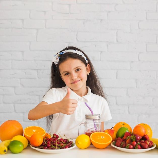 Nettes lächelndes mädchen mit den bunten früchten, die daumen herauf zeichen zeigen