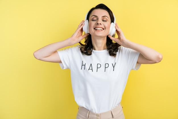 Nettes, lächelndes mädchen trägt kopfhörer. glückliche junge frau genießt musik in kopfhörern