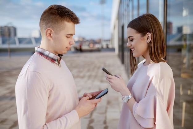 Nettes lächelndes paar gekleidet elegant stehend im freien und mit smartphones