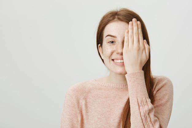 Nettes lächelndes rothaariges mädchen, das ihre sicht am optikerladen überprüft, bedeckt gesichtshälfte mit der hand