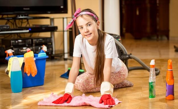 Nettes lächelndes teenager-mädchen, das wohnzimmer aufräumt und holzboden wäscht?