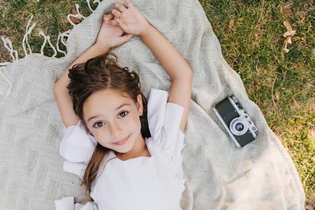Nettes leicht gebräuntes mädchen mit glänzenden schönen augen, die auf decke mit kamera während des sommerwochenendes aufwerfen. überkopfporträt des braunhaarigen weiblichen kindes, das auf dem gras liegt und träumt.