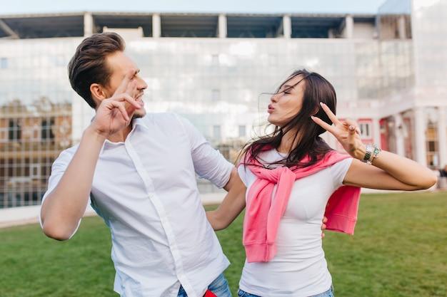 Nettes liebendes paar, das während des fotoshootings im freien am sommertag herumalbert