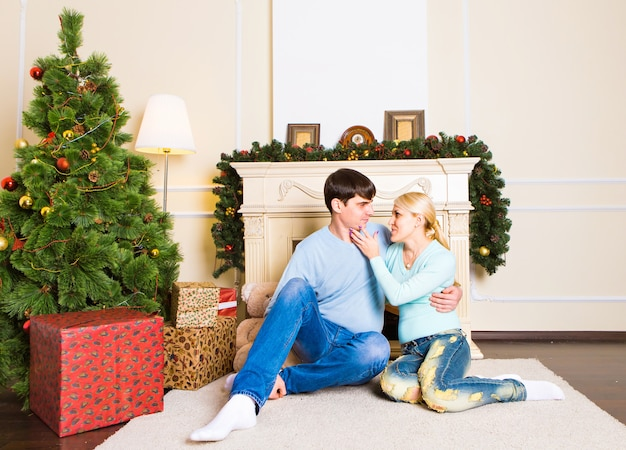 Nettes liebespaar, das auf teppich nahe dem kamin sitzt. frau und mann feiern weihnachten