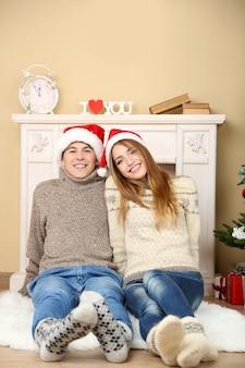 Nettes liebespaar, das auf teppich vor kamin sitzt. frau und mann feiern weihnachten