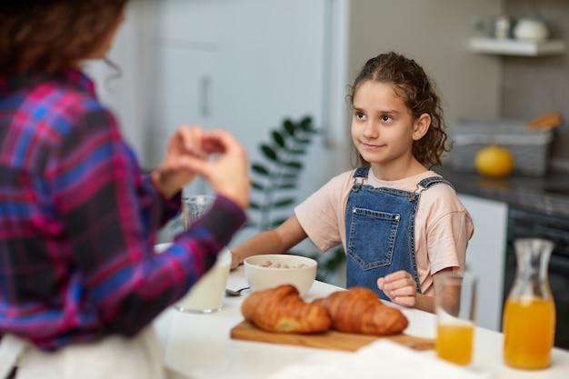 Nettes lockiges kleines mädchen in der küche, das mama lächelnd ansieht und herzsymbolform mit den händen tut.