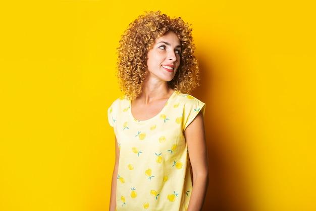 Nettes lockiges mädchen lächelnd schaut zur seite auf einem gelben hintergrund