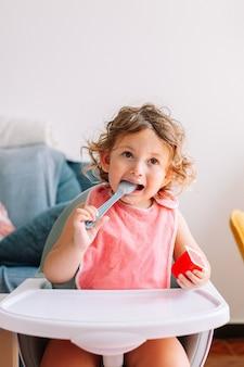Nettes lustiges babymädchen 2 jahre alt, das mit einem löffel im mund sitzt