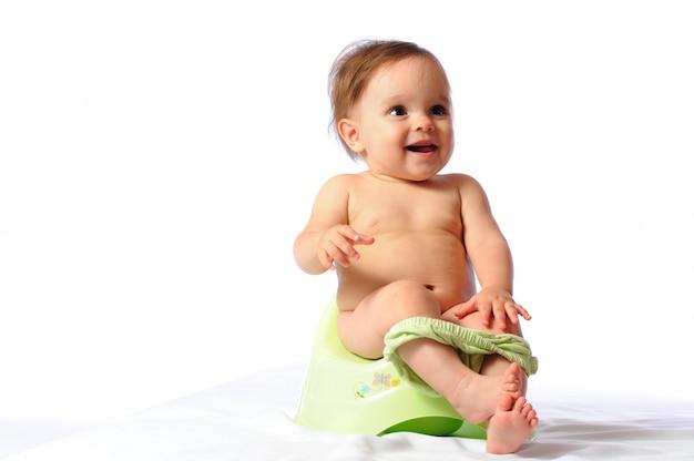 Nettes lustiges einjähriges baby, das auf grünem töpfchen sitzt.