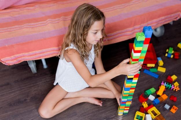 Nettes lustiges jugendliches mädchen, das mit den baubauklötzen zu hause errichtet einen turm spielt. kinder spielen. kinder in der kindertagesstätte. kind und spielzeug. familienlebensstil